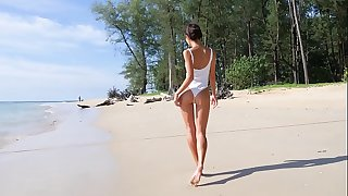 Sexy teenager on a beach teasing with her ass in one piece bathing suit
